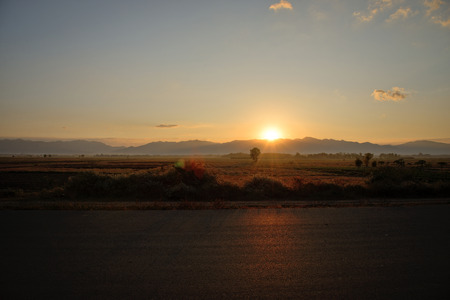 road side: Country road side view and mountain background at sunrise Stock Photo