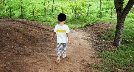 walking away: Little boy walking away in garden