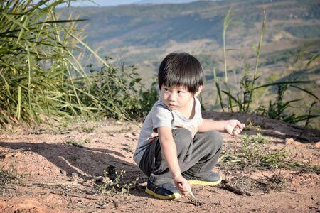 Kind jongen tekening in zand met een houten stok Stockfoto