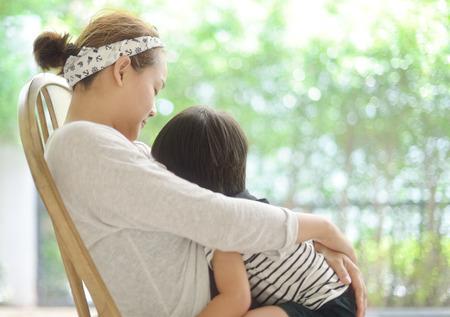 Glückliche junge Mutter ihren Sohn stillt