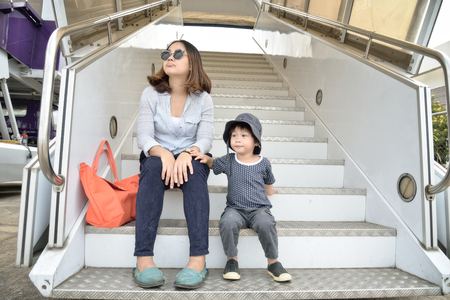 Young mother and son sitting on passenger boarding stairs at the airport