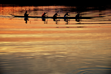 Teamarbeit von jungen Männern in einer Reihe Boot silhouetted bei Sonnenuntergang