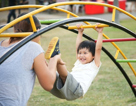 Happy mother holding her child hanging on playground