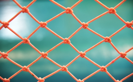 Orange nylon net on green background Standard-Bild