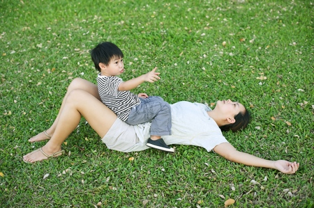 Little asian boy pointing and sitting on his mother in the park