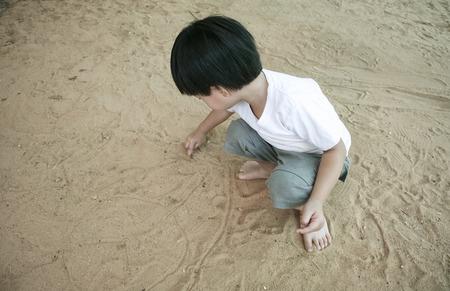 Little asian boy playing sand