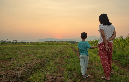 Mother standing with her son on the field and watching mountains at sunset : Viwe from back