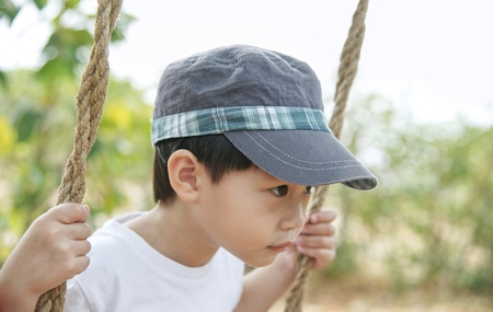 Little asian boy looking and playing on swing : Close up
