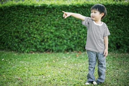 Little asian boy standing and pointing his finger in garden Imagens