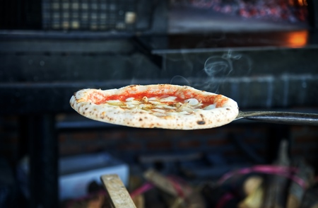 Pizza from oven by charcoal grill : Close up Standard-Bild