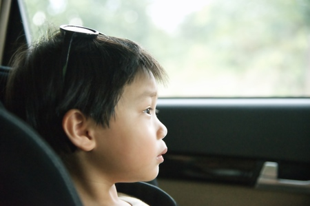 Little boy sitting in a child safety seat  in car and looking at window : Closeup
