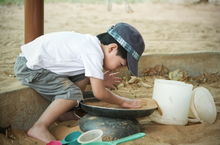 Little asian boy playing in the sandbox : Closeup 스톡 콘텐츠