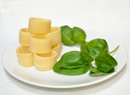 Pasta on a plate with basil leaves