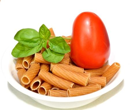 全粒小麦パスタのボウルにトマトとバジルを残します。 写真素材