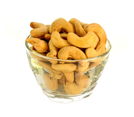 A glass bowl of cashews on a white background. photo