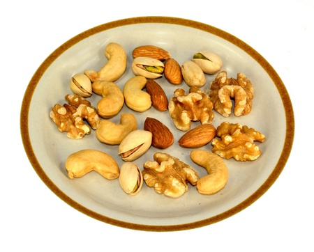 Walnuts, cashews, almonds and pistachios on a plate.