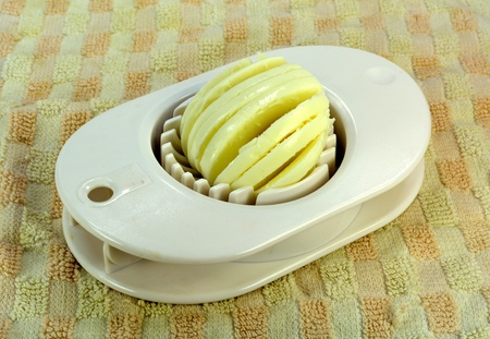 A hardboiled egg in an egg slicer  Stock fotó