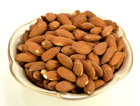 A small metal dish of shelled almonds.