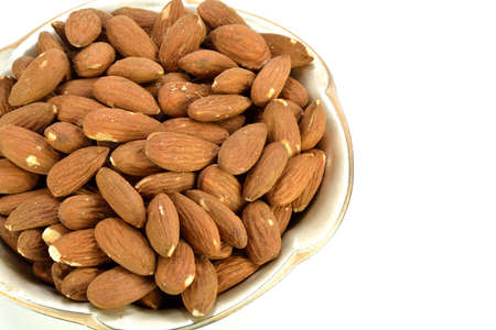 shelled: A small metal dish of shelled almonds.