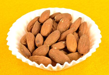 shelled: Shelled Almonds in a white paper cup  Stock Photo