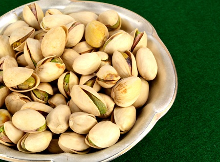 A small metal dish of pistachios in the shell. Imagens