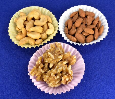 Cashews, almonds and walnuts in paper cups.