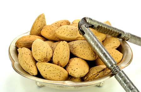 A small metal dish of almonds in the shell. Stok Fotoğraf