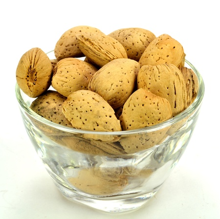 A small glass bowl of almonds in the shell. Stok Fotoğraf
