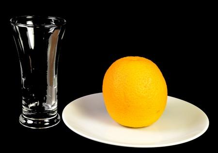 単一のオレンジと空のグラス。 写真素材