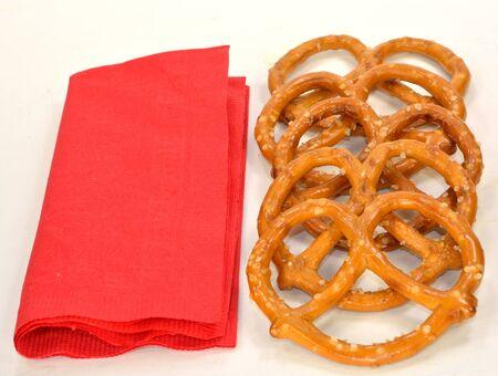 A group of pretzels next to a red napkin. Imagens