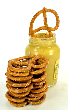 A stack of pretzels with a jar of mustard.