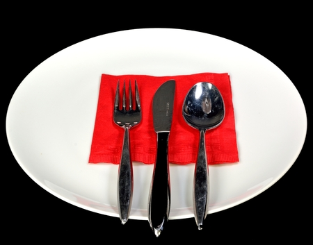 A white plate and utensils on a black background.