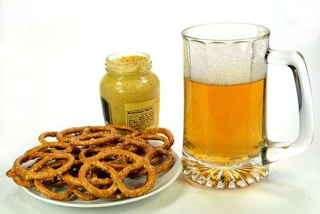 jarra de cerveza: Una pila de galletas con un tarro de mostaza y un vaso de cerveza. Foto de archivo