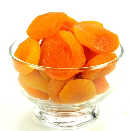 Apricots in a glass bowl on a white background. Stok Fotoğraf