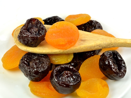 Dried apricot and a prune on a wooden spoon. 版權商用圖片