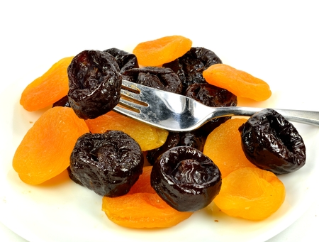 A prune on a fork with prunes and apricots in the background.
