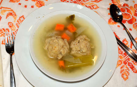 Motzo ball soup in a white bowl. photo