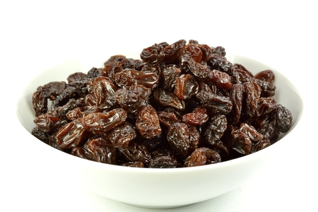 A bowl of raisins on a white background. Banco de Imagens