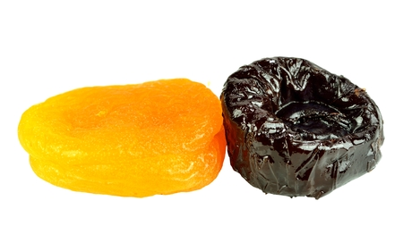 Dried apricot and a prune on a white background.