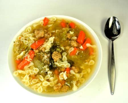 Bowl of italian wedding soup on a white .