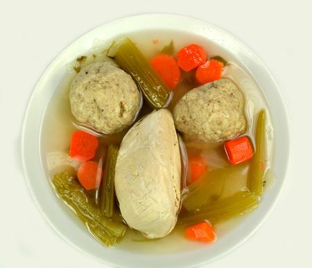 matzah ball: Matzo ball soup with chicken on a white.