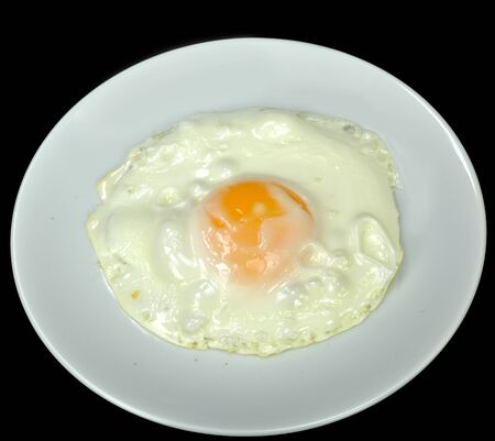 sunnyside: Fried (sunnyside) egg on a white plate against a black background.