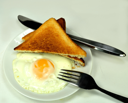 sunnyside: Fried egg with toast and a knife and fork.