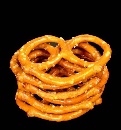 A stack of pretzels on a black background. Imagens
