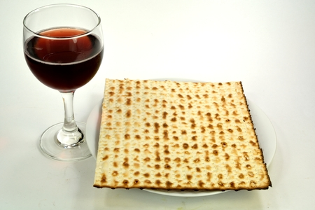 matzos: Matzos on a plate next to a glass of wine.