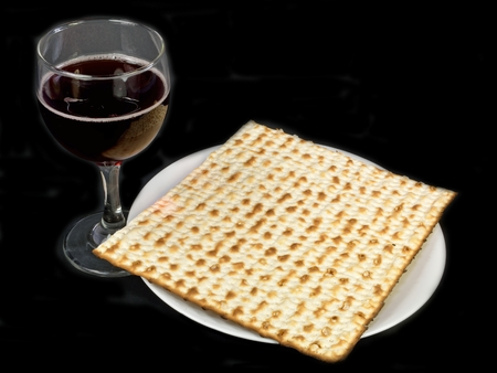 matzos: Matzo on a plate next to a glass of wine.