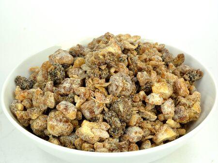 A bowl of chopped dates on a white . Stok Fotoğraf