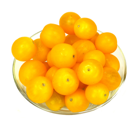 Glass bowl of yellow tomatoes on a white background