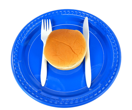 Hamburger bun on a blue plate with a knife and fork on a white background.