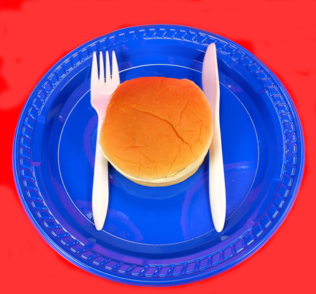 Hamburger bun on a blue plate with a knife and fork on a red background. Stock Photo
